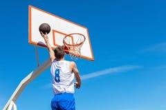 Junger Basketballstraßenspieler, der Slam Dunk macht Lizenzfreie Stockfotografie