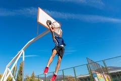Junger Basketballstraßenspieler, der Slam Dunk macht Lizenzfreie Stockfotos