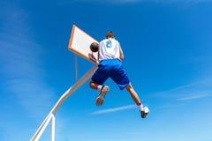 Junger Basketballstraßenspieler, der Slam Dunk macht Lizenzfreies Stockbild