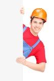 Junger Bauarbeiter mit dem Sturzhelm, der hinter einem Panel aufwirft Lizenzfreie Stockfotos