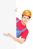 Junger Bauarbeiter mit dem Sturzhelm, der hinter einer Platte aufwirft Lizenzfreies Stockbild