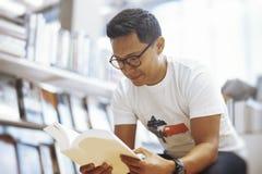 Junger bebrillter Mann, der in einem Buchladen- und Lesebuch mit Blinddeckel sitzt Stockbilder