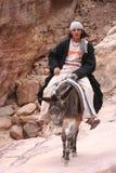 Junger Beduine, der seinen Esel reitet Lizenzfreies Stockbild