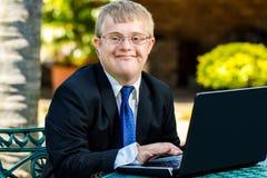 Junger behinderter Geschäftsmann, der mit Laptop arbeitet stockbild