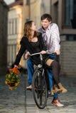 Junger beide Mann und Frau Reiten auf dem gleichen Fahrrad stockfotografie