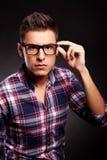 Junger beiläufiger Mann, der auf seine Sonnenbrillen sich setzt Lizenzfreie Stockfotos