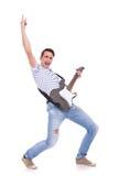 Junger beiläufiger Mann, der eine elektrische Gitarre spielt Stockbild