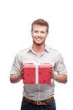 Junger beiläufiger Mann, der rotes Geschenk anhält Stockbilder