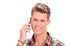 Junger beiläufiger Mann, der am Telefon spricht Stockbild