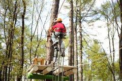 Junger Bergsteiger auf einem speziellen Fahrrad fährt auf Drahtseil Lizenzfreies Stockbild