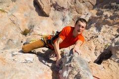 Junger Bergsteiger, der durch eine Klippe hängt Stockfoto