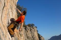 Junger Bergsteiger, der durch eine Klippe hängt Stockfotografie