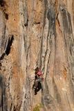 Junger Bergsteiger, der durch eine Klippe hängt Stockbilder