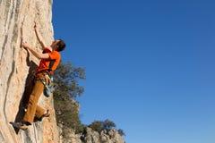 Junger Bergsteiger, der durch eine Klippe hängt Lizenzfreies Stockfoto