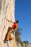 Junger Bergsteiger, der durch eine Klippe hängt Lizenzfreies Stockbild