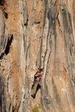 Junger Bergsteiger, der durch eine Klippe hängt Lizenzfreie Stockfotos