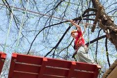 Junger Bergsteiger, der geht, auf eine Hängebrücke zu gehen Lizenzfreie Stockbilder