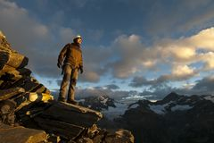 Junger Bergsteiger, der am Klippenrand steht lizenzfreies stockfoto