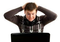 Junger überraschter Geschäftsmann, der an einem Laptop arbeitet Lizenzfreie Stockbilder