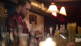 Junger Berufsbarmixer, der das rote Schutzblech setzt eine Zitrone in ein Glas mit rotem Alkohol trägt stock video footage