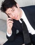 Junger Berufsgeschäftsmann auf Handy Stockfoto
