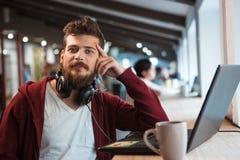Junger überzeugter Kerl, der im Büro unter Verwendung des Kopfhörers und des Laptops arbeitet Stockfotos