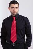 Junger besorgter Mann im schwarzen Hemd und in der roten Krawatte Lizenzfreies Stockbild