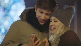 Junger Betrachtungshandy des glücklichen Paars in einer Stadt während der Winterweihnachtszeit Teilen Sie Gedächtnisse und Bilder stock video