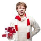 Junger blinzelnder Mann, der Weihnachtsgeschenke hält Lizenzfreies Stockfoto