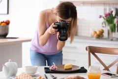 Junger Blogger, der Foto des Lebensmittels macht Lizenzfreie Stockfotos