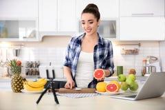 Junger Blogger mit den Früchten, die Video notieren Stockbilder