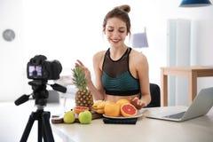 Junger Blogger mit den Früchten, die Video notieren Lizenzfreie Stockfotos