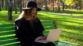Junger Blogger mit den roten Lippen im Hut mit breitem Rand Stockfotografie