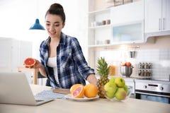 Junger Blogger mit Früchten und Laptop Lizenzfreie Stockfotos