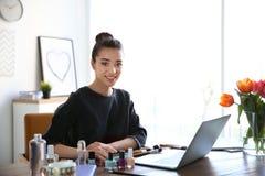 Junger Blogger mit Laptop und verschiedenen Kosmetik Stockbilder