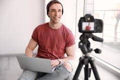 Junger Blogger mit Laptopaufnahmevideo Stockfotografie