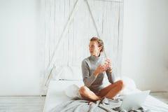 Junger Blogger oder Geschäftsfrau, die zu Hause mit Social Media, trinkender Kaffee am frühen Morgen im Bett arbeitet Lizenzfreies Stockbild
