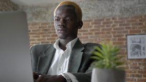 Junger blonder afrikanischer Geschäftsmann, der auf Laptop schreibt und die Kamera, überzeugt und erfolgreich, sitzend im Büro be stock video footage