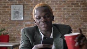 Junger blonder Afroamerikanergeschäftsmann, der auf dem Telefon und trinkendem Kaffee, sitzend im modernen Büro grast, überzeugt  stock video footage