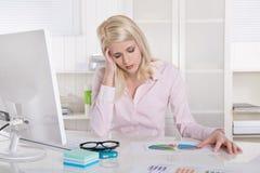 Junger blonder Auszubildender in der rosafarbenen Bluse mit Kopfschmerzen am Schreibtisch. Stockfotografie