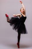 Junger blonder Ballerinamädchentanz und Aufstellung in den schwarzen Ballettröckchen- und Ballettschuhen auf grauem Hintergrund Stockfotografie