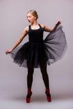 Junger blonder Ballerinamädchentanz und Aufstellung in den schwarzen Ballettröckchen- und Ballettschuhen auf grauem Hintergrund Stockbild