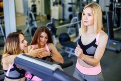 Junger blonder Betrieb auf der Tretmühle an der Turnhalle Das Lächeln mit zwei Eignungsfrauen motiviert sie Stockfoto