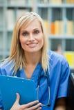Junger blonder Doktor bei der Arbeit lächelnd an der Kamera Stockbilder