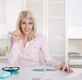 Junger blonder erfolgreicher Student am Schreibtisch im Büro. Lizenzfreie Stockbilder