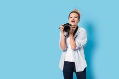 Junger blonder Fotograf genießt ihre Arbeit Stockbild