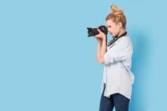 Junger blonder Fotograf macht ein Foto Stockbilder