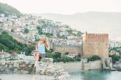 Junger blonder Frauentourist, der auf alter Festungswand von Alanya-Schloss sitzt Stockbilder