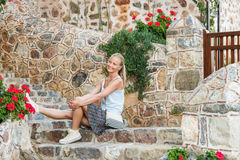 Junger blonder Frauentourist, der auf Steintreppe in der alten Stadtmitte von Alanya sitzt Lizenzfreie Stockbilder
