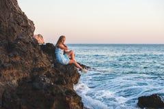 Junger blonder Frauentourist im blauen Kleid-sittig auf Felsen durch das Meer bei Sonnenuntergang Alanya, Mittelmeerregion, die T Lizenzfreie Stockfotos